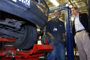 Sen. John Kerry chats with a student working on an automobile wheel alignment during Kerry's 2004 bid for the U.S. presidency.
