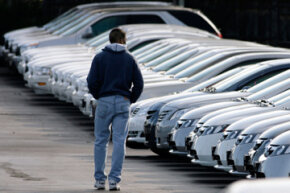 A shopper scans a long line of unsold General Motors lease-return vehicles on the lot of a Pontiac-GMC dealership in Aurora, Colo.