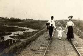 A husband and wife walk on railroad tracks as each holds a hand of their young daughter. Trains made long distance travel much faster and more comfortable and were the preferred way to get around before cars were introduced.