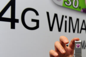 A woman displays a fourth-generation WiMAX device during a exhibition at a convention centrer in Taipei in 2010.