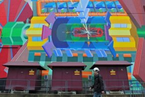 A CERN worker cruises past a painted representation of the LHC's ATLAS experiment on Dec. 13, 2011, in Geneva, Switzerland.