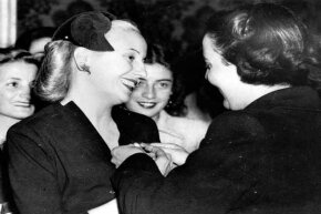 Eva Peron (left) being presented with an insignia by the volunteer workers of the Institute for Work of Argentina.