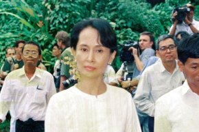 In a photo circa 1989, Aung San Suu Kyi walks inside her house on in Yangon, Myanmar surrounded by supporters.