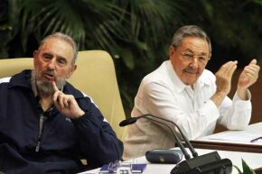 Fidel Castro (left) makes a point during the Cuba's 6th Party Congress session in 2011; his brother Raul looks on.