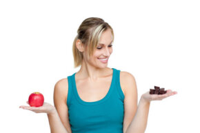 Woman deciding between chocolate and fruit