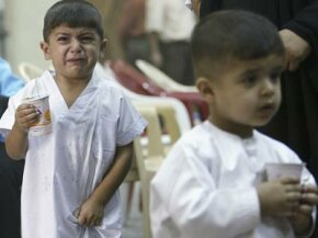 An Iraqi child cries as he stands in line to be circumcised July 14, 2005 in Baghdad.