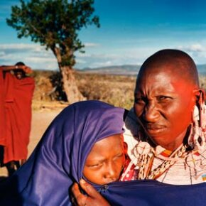 After this girl's circumcision in November 2004, she is shown to neighbors to prove the surgery was successful. In the background is her future husband. She will be married immediately after her healing period is over.