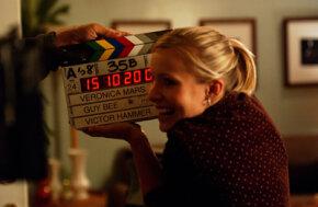 Actress Kristen Bell holding a digital slate.
