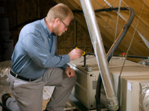 Service man kneels beside a furnace in a home attic, to inspect it for before winter usage.