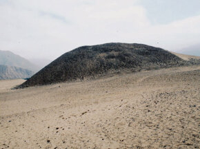 A pyramid at Caral, Peru, is shown buried under a layer of windblown sand and collapsed rock.