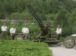 Staff members from Beijing's Xiangshan Weather Modification Practice Base stand next to a two-pipe cannon used for rain reduction and cloud dispersion.