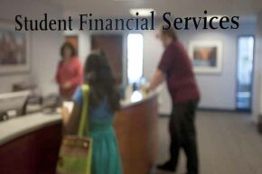 Students visit the financial aid office at Northeastern University in Boston. The competing interests of the individual colleges often prevent a university from making necessary budget cuts.