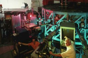 Administrator Jim Greene (center) watches as a physicist monitors a Tokomak during a fusion experiment in a laboratory at the University of Texas-Austin.