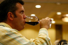 A guest tries some wine at a Colorado wine festival.