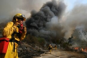 Firefighter Elizabeth Ferolito keeps an eye on a controlled backfire in Irvine, California, set to protect homeowners as a wildfire rages.