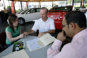 A customer signs the purchase contract in front of a salesman at Commonwealth Motors in Lawrence, Mass.