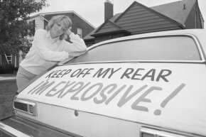 Patty Ramge appears dejected as she looks at her Ford Pinto where she put a sign on the rear of the automobile because of the firey accidents involving Pintos.