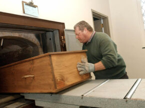 Crematory operator Joe Bancewicz places a coffin into the retort at Mount Auburn Cemetery, Feb. 21, 2002, in Watertown, Mass.