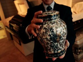 Death Image Gallery Funeral director Peter DeLuca, owner of Greenwich Village Funeral Home, holds a cremation urn in the showroom of his funeral parlor in New York City. See more death pictures.