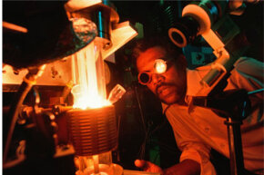 Circa 1975: Senior lab technician Charles Young watches sapphire crystals growing in a crystal grower at the Corning Glass Canada Road plant. The crystals were used in sodium vapor lamps.