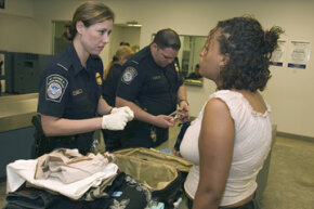 A CBP office checks a passenger's luggage and documents.