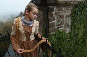 Rapunzel, actually 13-year-old actress Anna Helver, lets down her hair from a tower balcony at Trendelburg Castle, Germany, in 2012, around the 200th anniversary of the publication of Grimm's fairy tales.