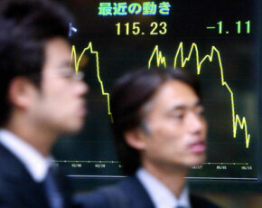 Japanese businessmen pass a foreign exchange rate chart in downtown Tokyo.