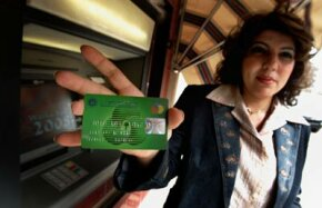 Banks in Baghdad have started issuing debit cards to customers, as advertised by this employee of Warka Bank on March 11, 2008.