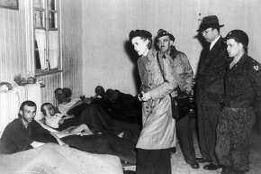 Writer and ambassador Claire Boothe Luce visits a surviving deportee from the Buchenwald concentration camp afflicted with tuberculosis in 1945.