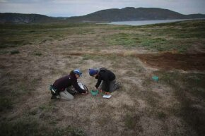 Julia Bradley-Cook (L) and Leehi Yona use a device to read the amount of CO2 that is being released from the warming ground on July 10, 2013 in Kangerlussuaq, Greenland.