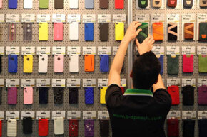 An employee arranges Apple iPhone cases at the D-Parts stand at the Internationale Funkausstellung (IFA) 2012 consumer electronics trade fair in Berlin, Germany.