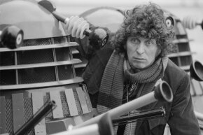 "Actor Tom Baker, as the Doctor from the BBC science fiction TV series ""Doctor Who,"" poses with the Doctor's arch enemies, the Daleks, in 1975."