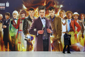 A security guard walks past a giant Doctor Who poster at the 'Doctor Who 50th Celebration' event in London, England.