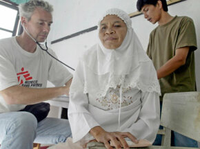 A doctor from Doctors Without Borders performs a checkup in Indonesia.