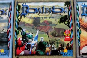 The front cover of the Dominion box, with artwork by Matthias Catrein. The game is flanked by expansions Seaside and Intrigue. We can't promise your friends will all love the game so much that you'll have to initial your copies like a summer camp towel. See more pictures of toys and games.