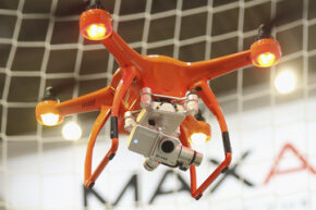 A MaxAero quadcopter drone flies with a camera attached at the 2015 CeBIT technology trade fair.