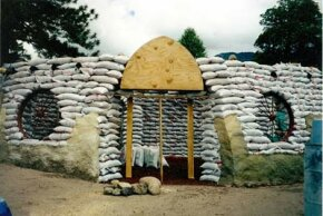 This earthbag home has a wooden door form and wagon wheel window forms.