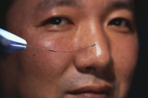 Ryo Ota, a group manager for the Olympus Optical Company in Japan, holds a shape memory alloy tube. Engineers think these smart materials could prove handy in preventing earthquake damage to buildings.