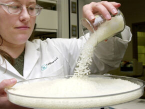 A quality assurance analyst pours pellets of corn plastic into a dish.