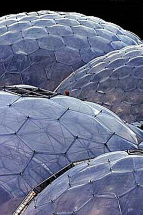 The giant dome structure of Eden's greenhouse roof dwarfs a worker installing the transparent panels.