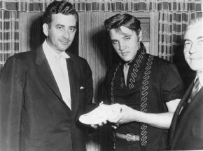 Elvis Presley and merchandiser Hank Saperstein show off an Elvis sneaker, one of many Elvis collectibles. See more Elvis pictures.