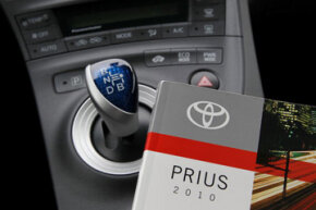 An owner's manual is shown on the console of a 2010 Toyota Prius hybrid car in San Francisco, Calif.