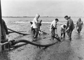 Firemen work to pump crude oil off the coast of France after the Amoco Cadiz oil spill.