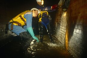 Thames Water Utilities sewer workers inspect a sewer beneath the streets of London.