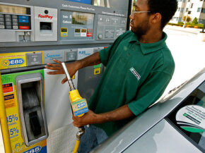 An Enterprise car rental employee gases up a Chevrolet with E85 flex-fuel in Washington, D.C. More eco-conscious consumers are demanding cars with higher gas mileage from auto rental companies. See more pictures of AFVs.