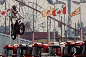 Daredevil motorcyclist Evel Knievel sails over seven Mack trucks during a practice jump in the open-air Canadian national exhibition stadium in Toronto, Ont., on Aug. 20, 1974. See more extreme sports pictures.