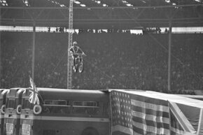 Evel Knievel approaches the landing ramp with his motorcycle during his unsuccessful effort to leap over 13 buses in London, England, on May 25, 1975.