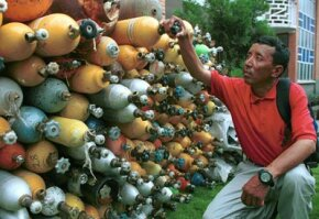 Trash, especially from abandoned equipment like oxygen cylinders, is a huge problem at Mount Everest. Here Appa Sherpa, who has climbed Everest 11 times, looks at some cylinders collected by the Nepalese government.
