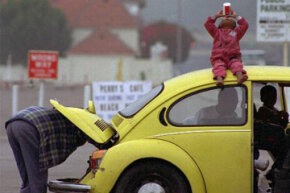 James L. Edward (left) checks the engine of his 1973 Volkswagen in Santa Monica, Calif., to make sure he doesn't have any trouble before making the return trip home to Alabama with his 2-year-old daughter Nahndi Malbrongh (on top of car).