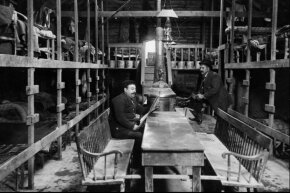 Two workers relax in the immigrant sleeping quarters of the New York State Barge Canal construction project in 1909.